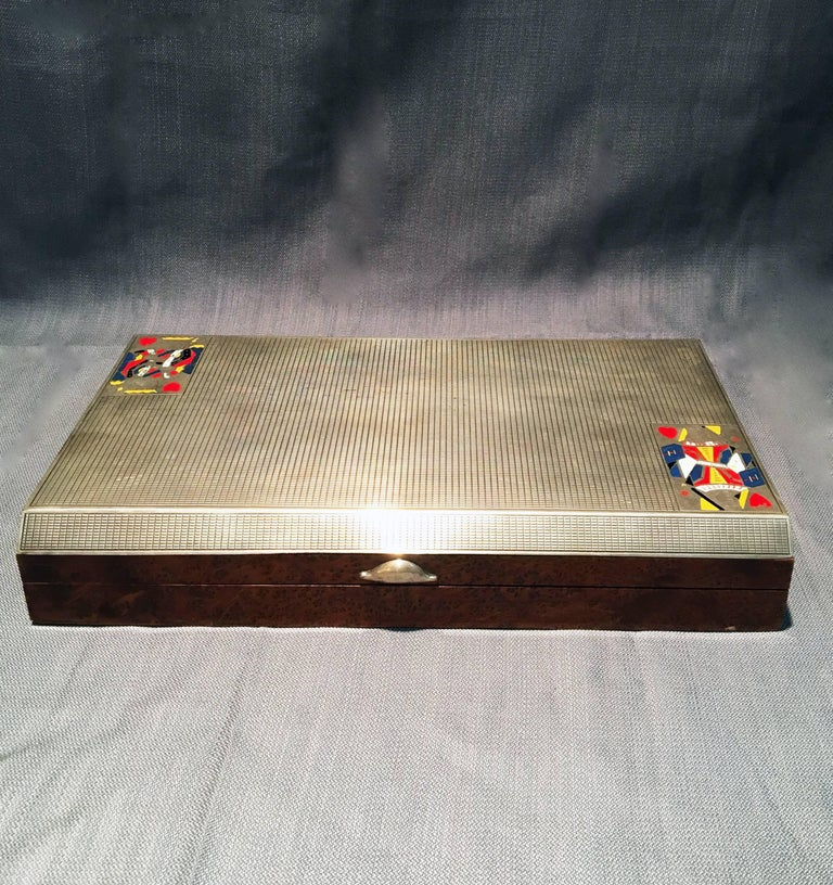 This 1920's 800 silver and walnut game case featuring the king and queen of hearts comes with playing cards, chips, and dominoes. The case has been stamped with a hallmark.