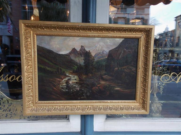 American oil on canvas of landscape depicting mountains, meadows, and a stream in the original mounted foliage gilt frame. Late 19th Century.