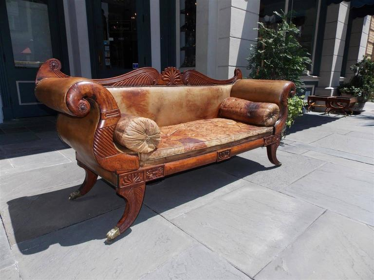 Caribbean Regency mahogany leather sofa with serpentine gadrooned carving , centered decorative floral shell back, flanking scrolled medallions and fluted carved arms with bolster side pillows. Sofa has a lower carved centered floral skirt , and