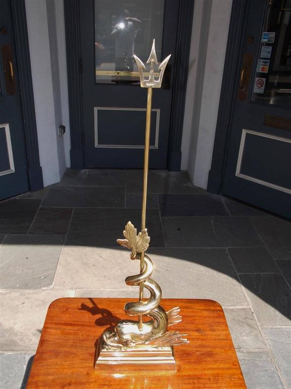 English brass winged dolphin intertwined trident doorstop resting on molded edge rectangular base, Early 19th Century.