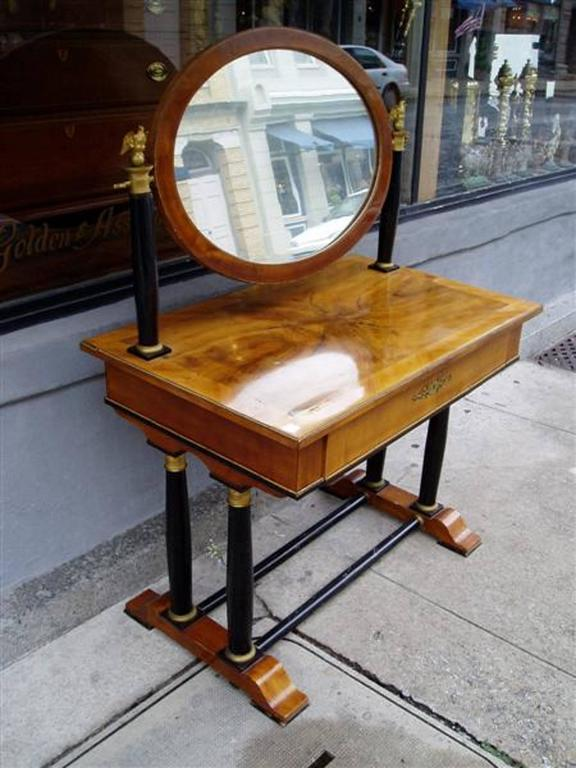 Viennese flame birch veneered dressing table with flanking bronze eagle capitals mounted on ebony columns supporting an adjustable oval veneered framed mirror, centered drawer with beading, ormolu escutcheon and fitted interior, all resting on four