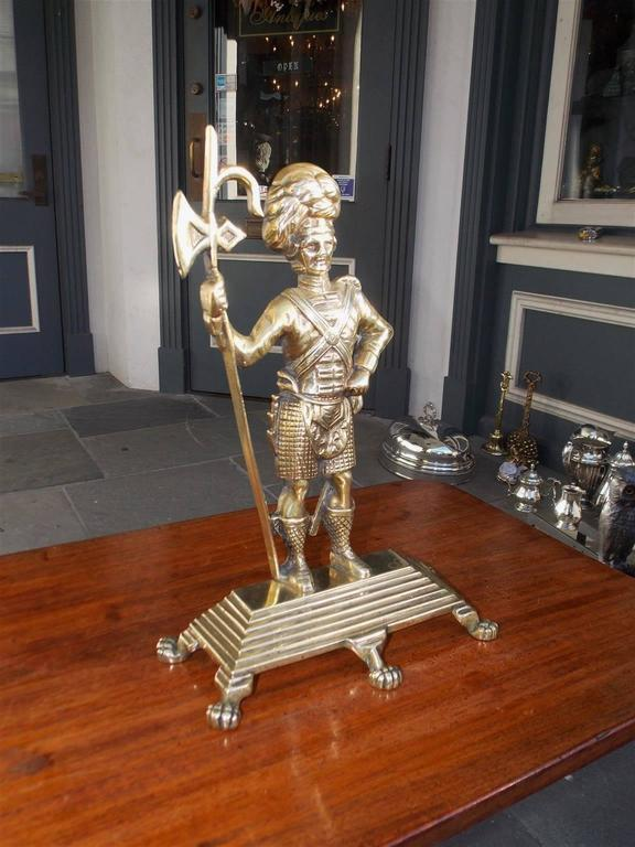 Scottish brass Highlander Royalty Guard doorstop dressed in full military attire standing on a step back rectangular base with lions paw feet, Mid-19th century.