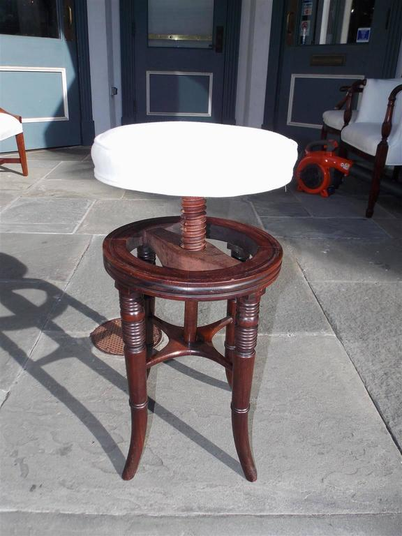 English Regency mahogany piano stool with a swivel seat, carved molded edge and terminating on the original splayed ringed legs with connecting stretchers. Stool has been upholstered in white muslin, Early 19th century.