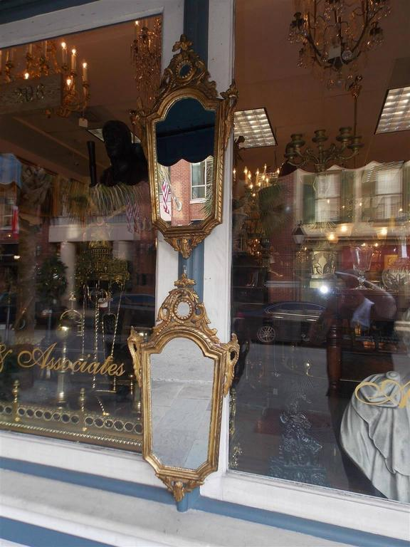 Pair of Italian gilt carved wood wall mirrors with floral carved cartouche, flanking scrolled foliage, interior egg & dart motif, and terminating with a lower floral pendant. Mirrors retain the original glass and wood backing. Early 19th century.