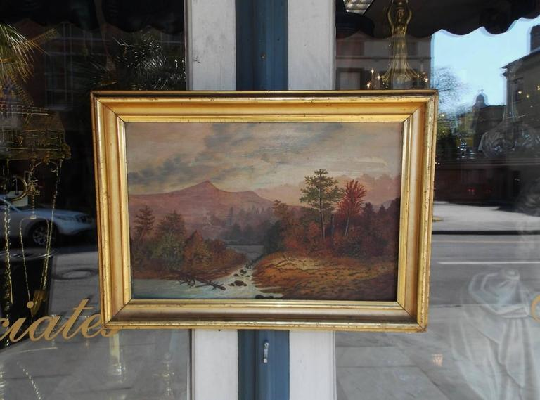 American school oil landscape on academy board in the original gold gilt molded frame. Landscape depicts Hudson Valley with mountains in the background, trees in the foreground and a flowing rocky stream, Early 19th century. Inscribed Mrs. Demming