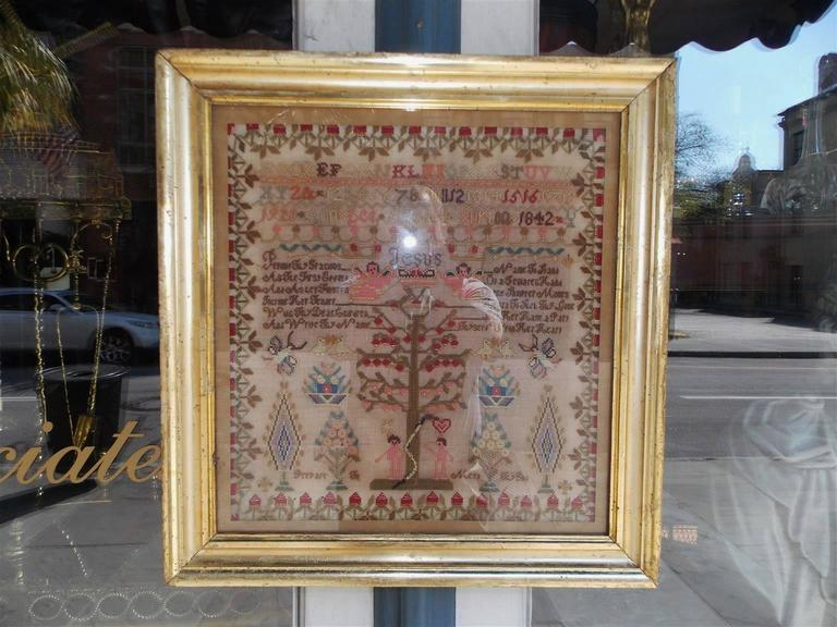 American needlepoint christian themed sampler in the original gold gilt frame under glass. Tree of knowledge good and evil. Adam and Eve with the serpent. Worked by Ann Lee Burtin, age 14, dated 1842.