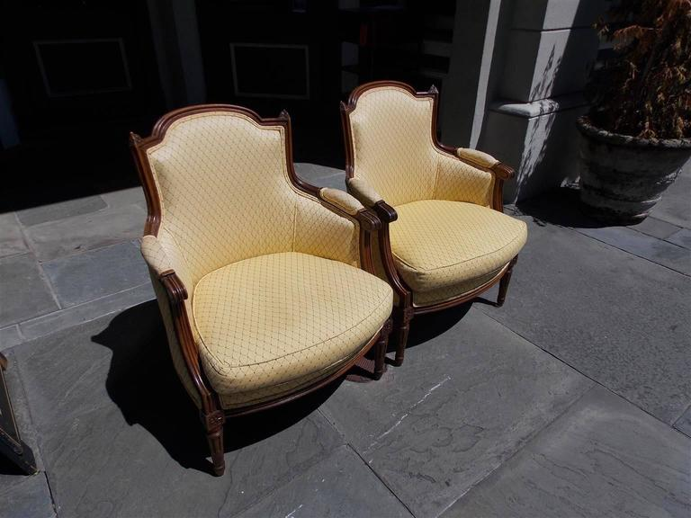 Pair of Italian Walnut Bergere armchairs with carved molded reeded edges, floral corner decorative finials, flanking scrolled arms, floral corner rosettes, and terminating on the original carved fluted ringed legs. Chairs are upholstered in a cross