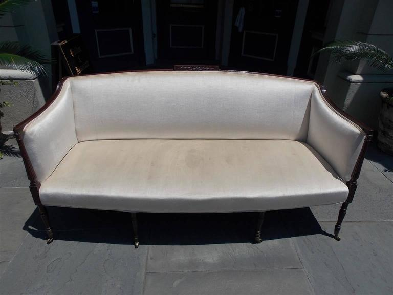 American mahogany Sheraton style sofa with an arched back , carved centered ribbon with graduated bell flower cartouche , sweeping scrolled reeded arms , terminating on fluted, reeded, squared tapered legs, with the original brass casters. Late 19th