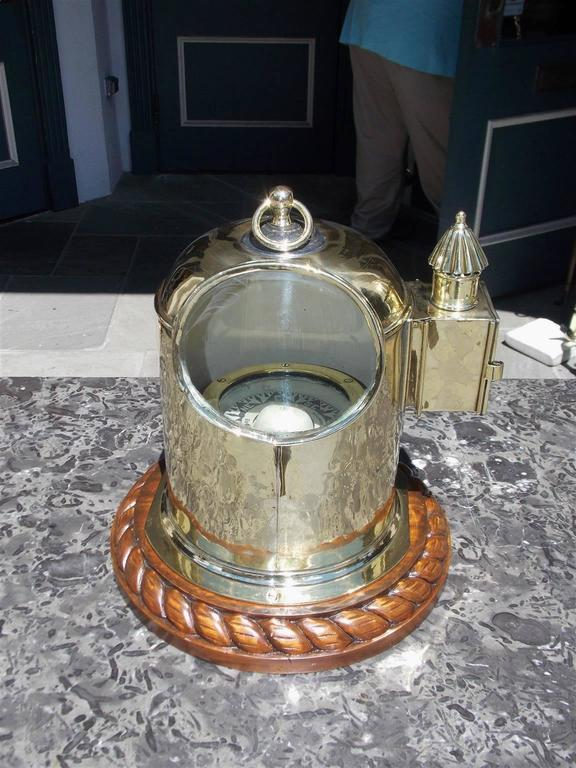 English yacht binnacle mounted on a mahogany rope motif base, oval glass viewing port, with the original removable brass vented side light and carrying handle. Binnacle is fitted with an interior compass submerged in alcohol signed Cope,