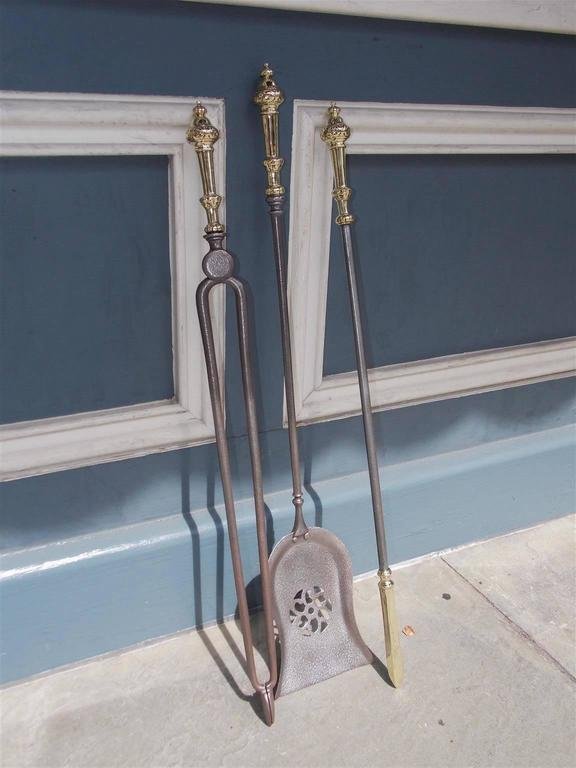 Set of three English polished steel and brass fire place tools with decorative urn finials and foliage handles. Set consist of pierced floral shovel, tong, and brass tipped poker for stoking the fire place, Early 19th century.