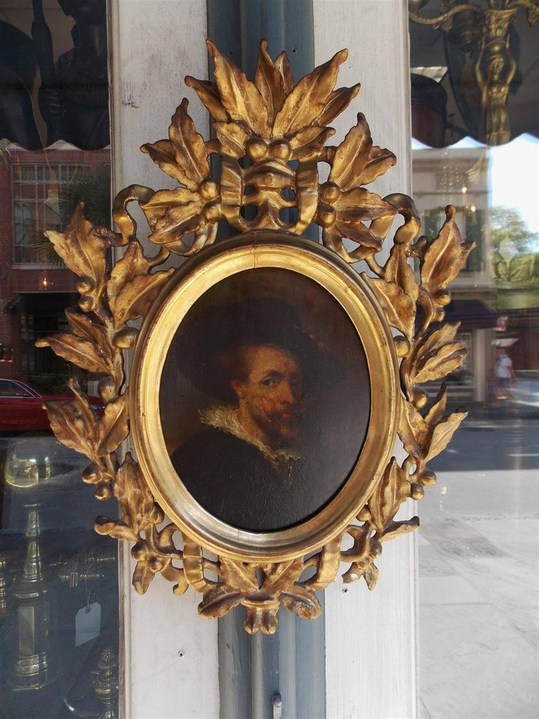 Italian oval oil on board gilt carved wood portrait of a gentleman in the original floral and berry frame, 18th century.