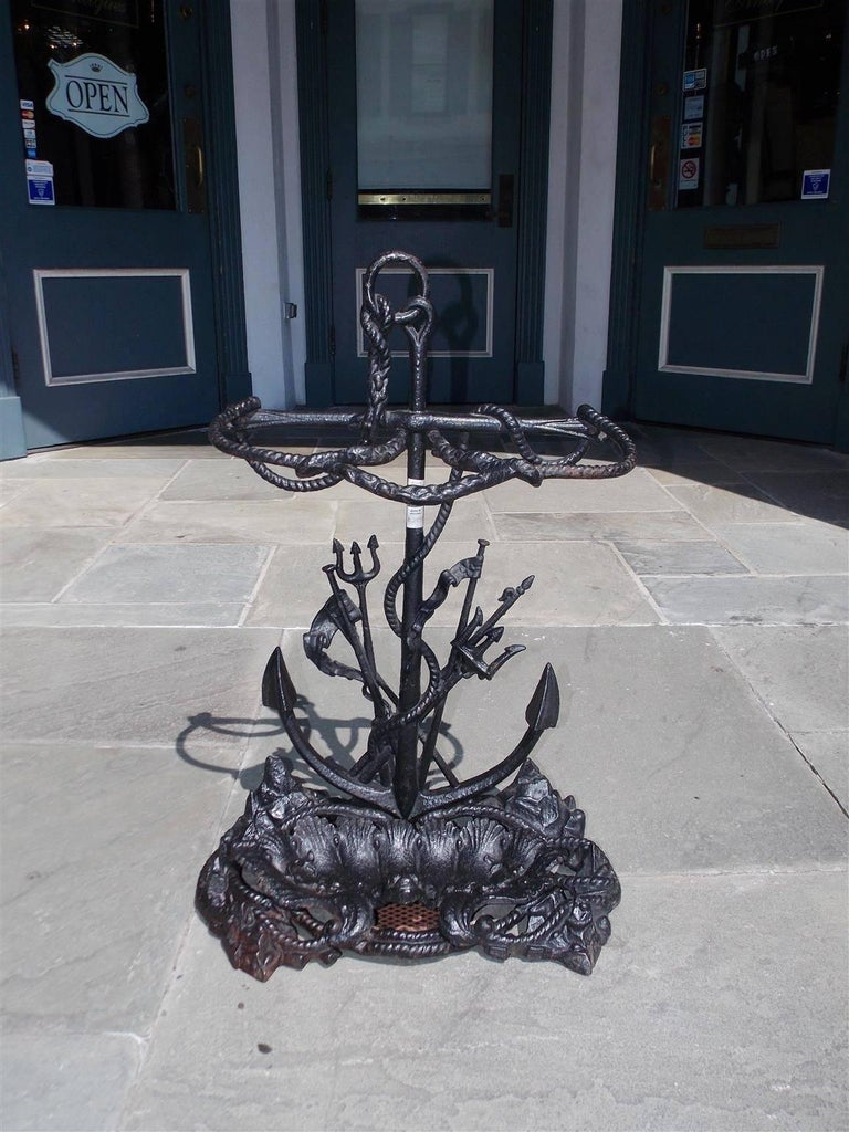 American cast iron nautical umbrella stand with centered anchor ring attached and intertwined with rope, two smaller tridents with spears, and resting on a stylized rocky base with a removable shell and dolphin motif pan, Mid-19th century.