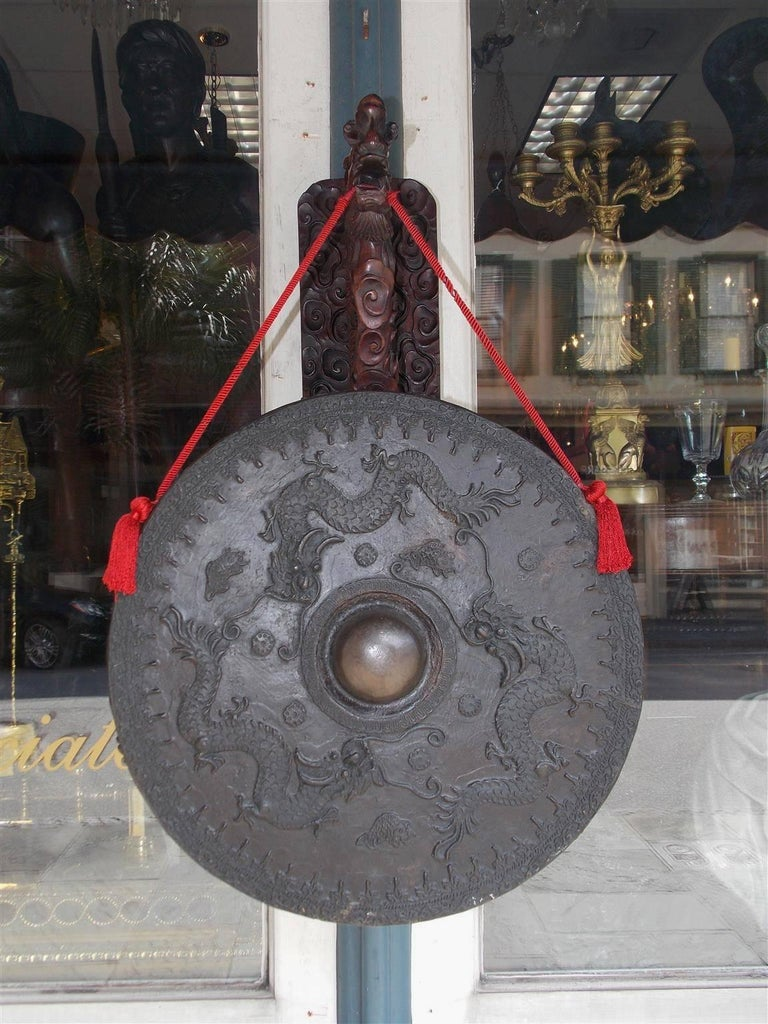 Chinese rosewood circular temple gong with a decorative carved wall-mounted dragon bracket supporting a braided silk rope bronze gong with decorative dragons, floral medallions, and Koi fish. Gong has the original mallet. 19th Century. Wall-mounted