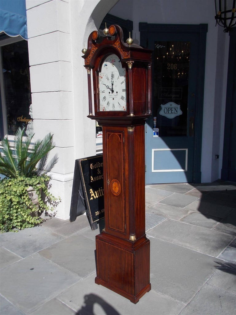 Scottish mahogany eight day tall case clock with three sphere brass finials, a swan neck satinwood inlay patera pediment, intricately carved fretwork, over an arched door with flanking Corinthian fluted columns, Satinwood inlaid patera trunk with