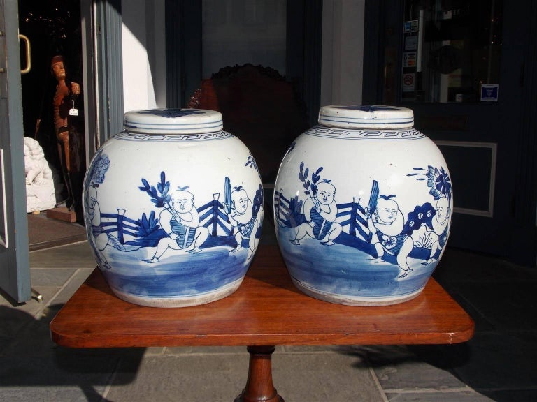 Pair of Chinese blue and white porcelain glazed decorative figural and floral ginger jars with the original removable lids, 20th century.