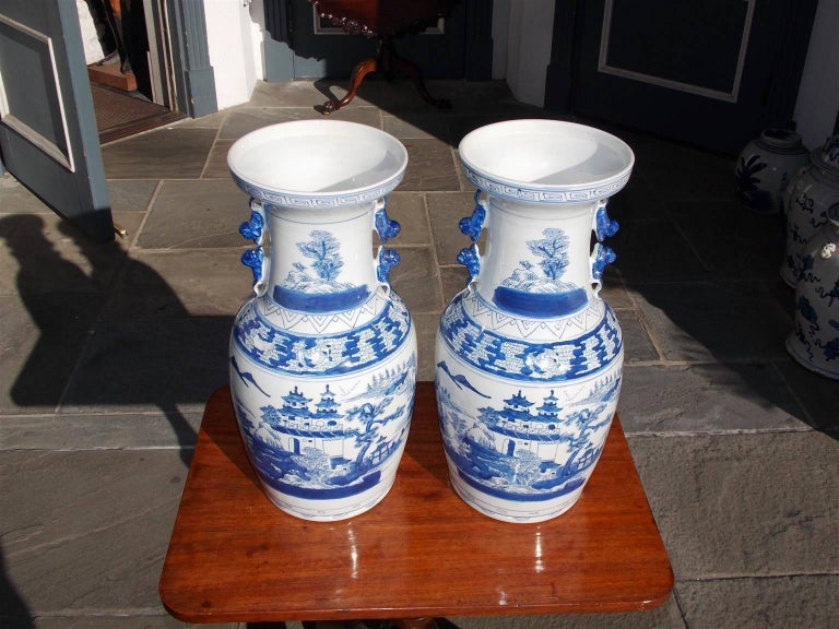 Pair of Chinese porcelain glazed blue and white temple jars with hand-painted Greek key borders, flanking foo dog side handles, and decorative hand-painted pagoda, mountain, and landscape scenes. 20th century.