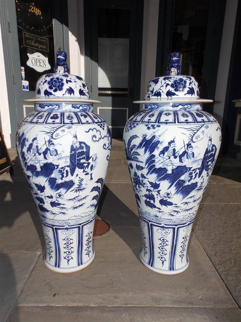 Pair of monumental Chinese porcelain glazed vibrant painted blue and white temple urns with removable foo dog finial lids, warriors in battle mounted on horses, landscapes with cascading streams, and resting on decorative floral tapered bases, 20th