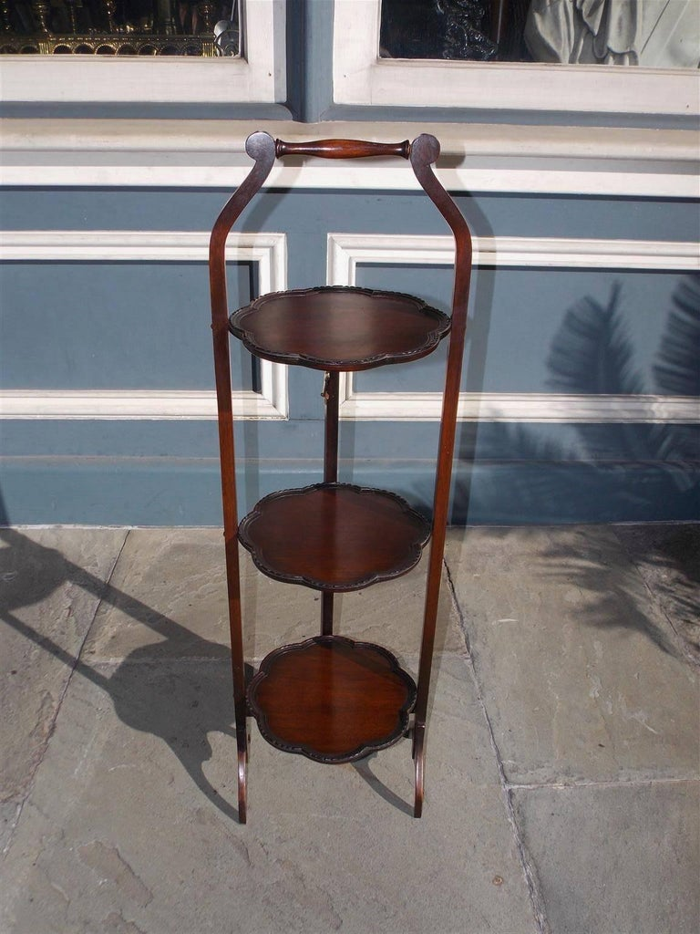 English mahogany three-tiered folding muffin stand with a centered turned bulbous handle, flanking scrolled supporting side rails, carved scalloped molded edges, and terminating on four scrolled spider legs, Mid-19th Century.