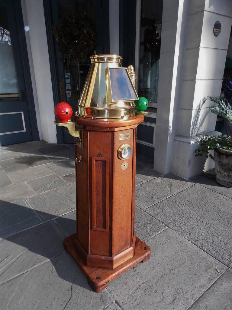 This highly desirable and fine nautical instrument is made of carved mahogany with a brass and glass hood covering a gimbaled compass and flindler's tube with cap. The eight sided binnacle was deck mounted and has painted cast iron port and