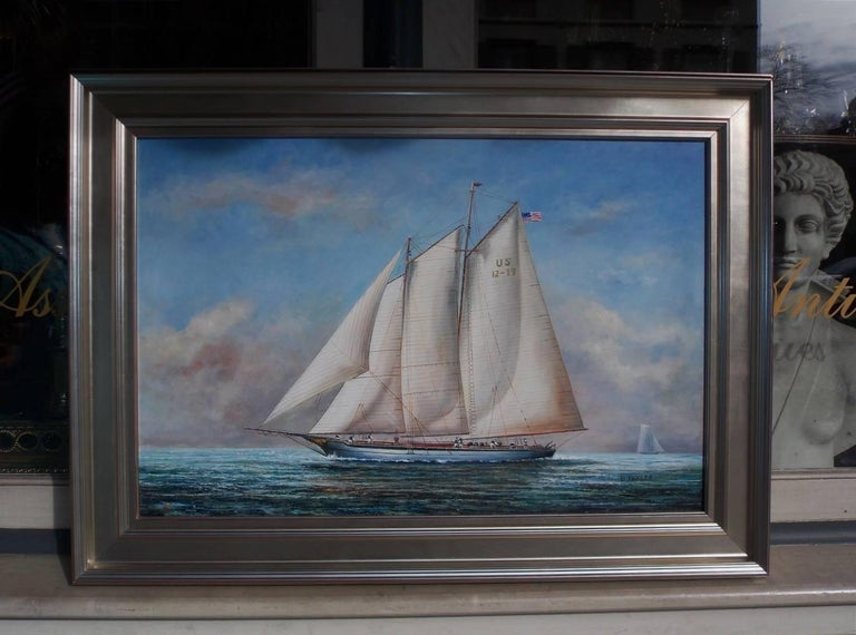 American nautical oil on canvas of two masted schooner yacht under full sail with American flag, crew on deck, second vessel in distance, and mounted in a silver gilt frame, Early 20th century. Signed D. Thyler.