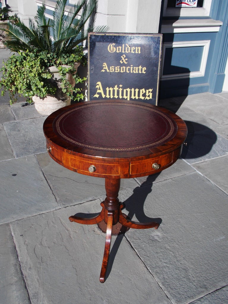 English Regency mahogany circular drum table with a red leather top and gilt tooling, alternating satinwood inlaid drawers with the period floral brasses, carved turned bulbous ringed pedestal , and terminating on the original splayed legs with ball