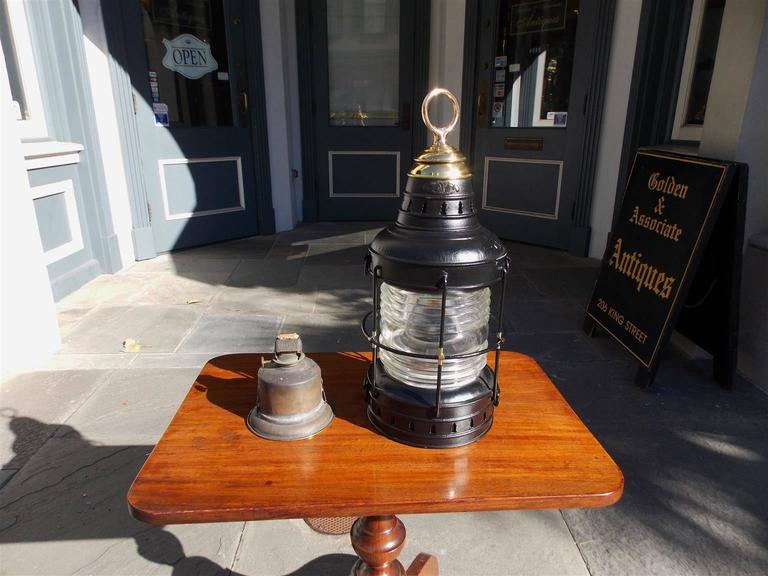 American painted polished steel and brass single ship anchor lantern with original Fresnel lense, hoisting ring,  protective cage, and original oil burner. Late 19th century Signed Wilcox- Crittenden and Company, Middle town,
