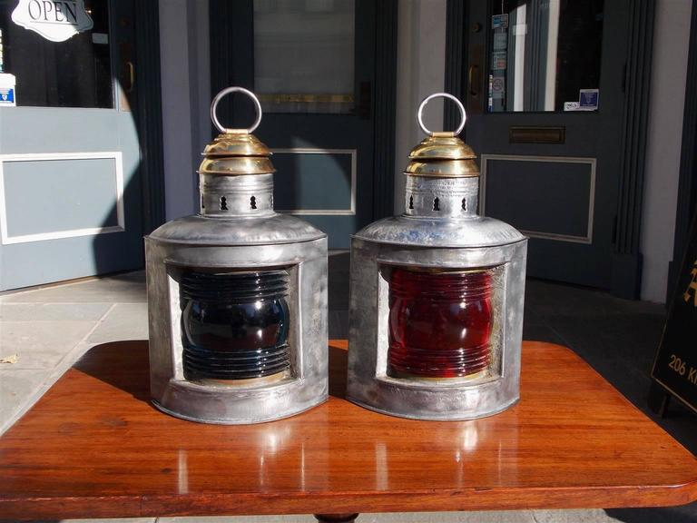 Pair of American polished steel and brass nautical ship lanterns with original port and starboard Fresnel lenses with hoisting rings .  Late 19th Century .