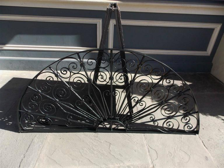 American wrought iron demi-lune ten panel window transom / gate with pleasing decorative scroll work motif.  Early 19th Century