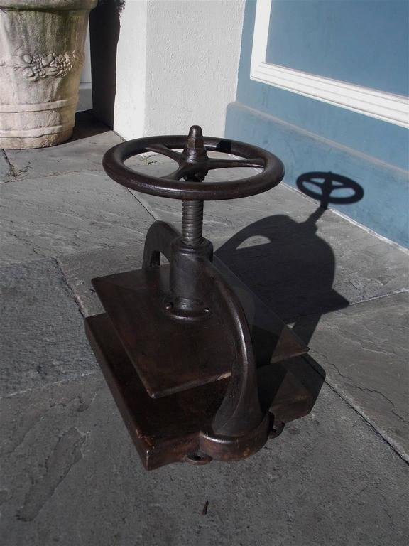 American cast iron book press with rotating circular three spoke wheel, scrolled arms, and rectangular press.  Early 19th Century
