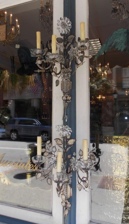 Pair of FrenchMaison Baguès style three arm crystal sconces with upper and centered floral medallions, bead work, leaf foliage, and crystal cup bobeches. Sconces were originally candle powered and have been electrified, Late 19th Century.