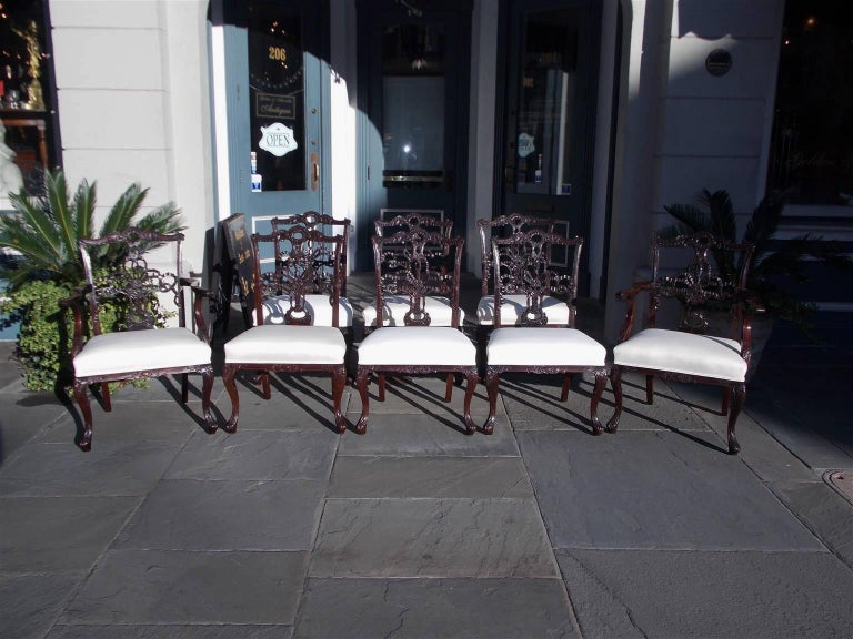 Set of eight English Chippendale mahogany dining room chairs with a serpentine carved acanthus and ribbon cresting rail, rolled foliage ears, molded edge stiles, ornate carved ribbon splat backs, gadrooned shoes, scrolled acanthus arms, upholstered