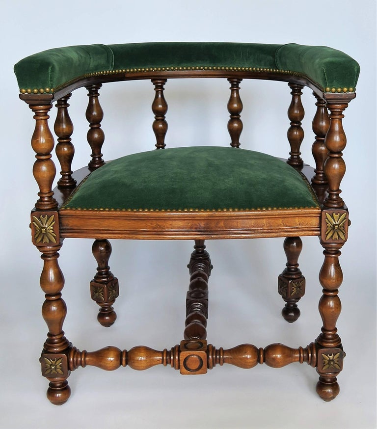 Decadent and refined, this pair of elegant barrel back Jacobean styled armchairs or library chairs have detailed hand-turned legs and back. The oakwood is rich with gorgeous patina, brass escutcheons medallions on each leg corner complete the look.