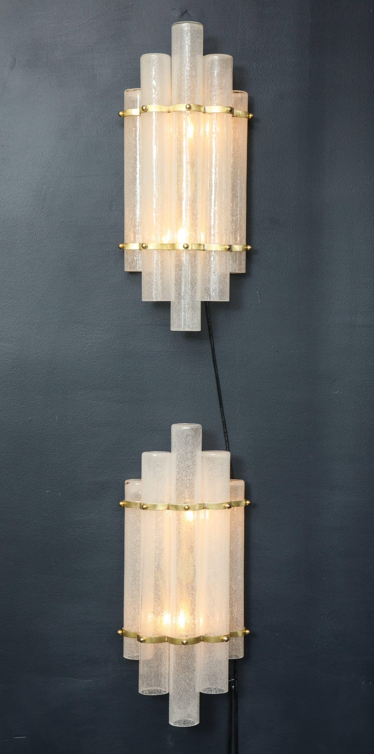 "Magnificent Pair of Murano Glass sconces in handblown ""pulegoso"" white glass tubes with brass frames. The thick glass gives a beautiful glow set off by the delicate brass rings holding the cascading tubes.  Wired for U.S. use.  This pair of Murano"