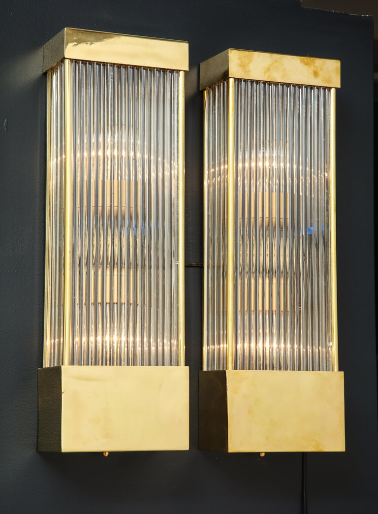 Pair of clear glass rods with brass frame rectangular sconces. Handcrafted in Venice. Rewired for U.S. use. Each light requires two medium socket lightbulbs. Clean lines make this pair of sconces the perfect addition to any decor. 