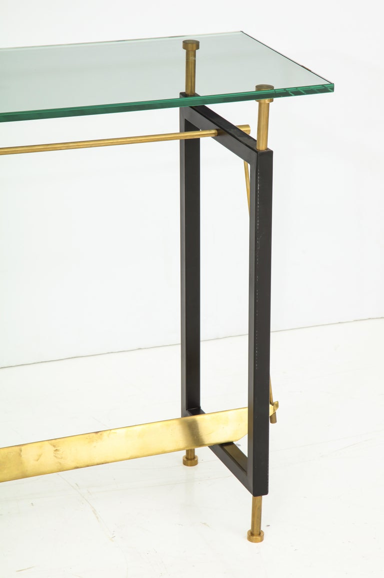 This elegant and Minimalist console was custom-made in Italy and is a one of a kind design. The base is made of black painted iron and natural brass frame which is architectural in design. Solid and substantial, the console is finished with a thick