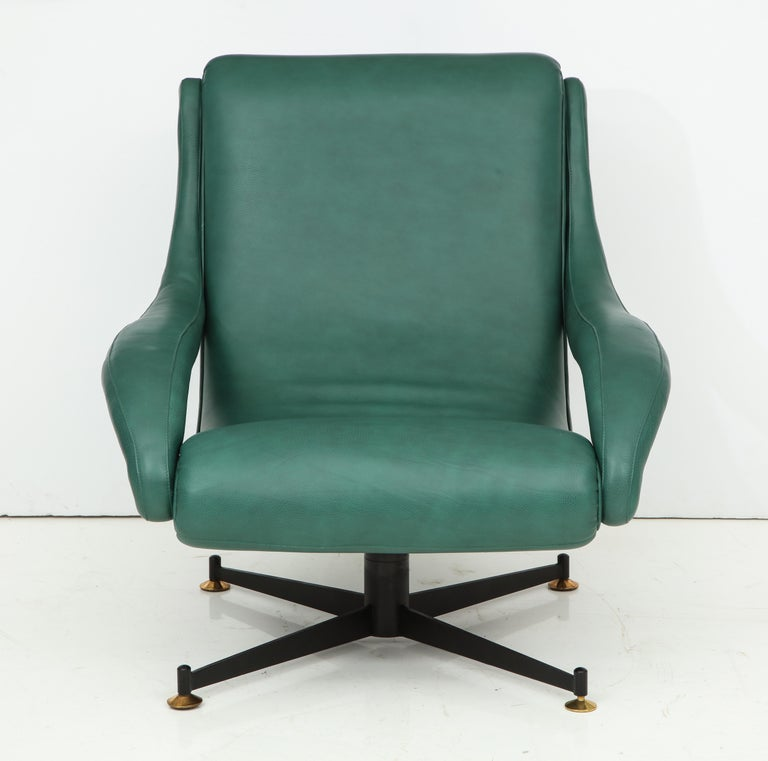 Pair of Italian Mid-Century Modern lounge chairs, original four star iron base with brass feet with vintage patina but in perfect condition, newly reupholstered in Italian green leather by Gucci, circa 1950. This pair of lounge chairs is attributed