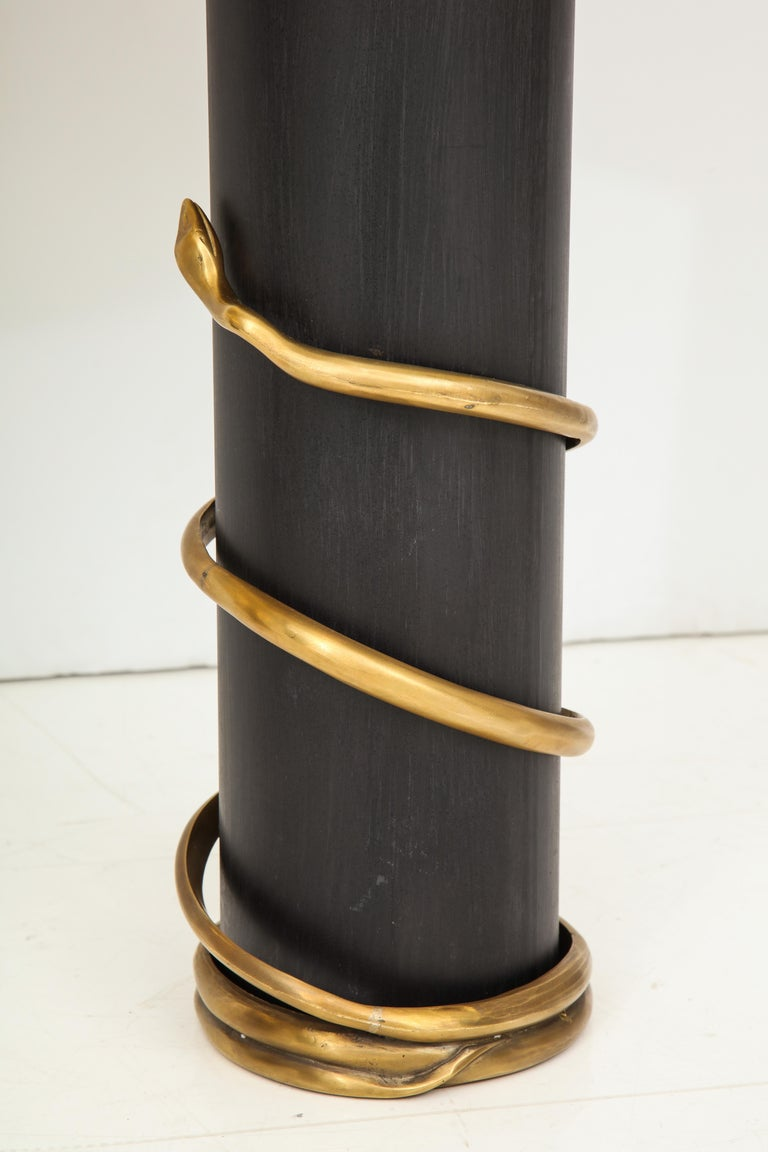 Pair of unique black enameled metal cylinder shaped base which is wrapped by a solid brass snake. Artistic and sculptural in nature and handcrafted in Italy. Custom made Italian black drum lampshades lined with metallic gold are included. An