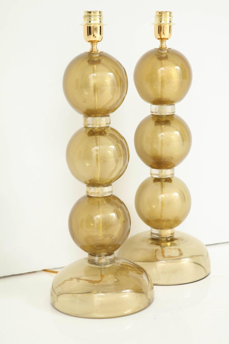 Pair of seductive gold lamps made consisting of clear glass infused with 23-karat gold, creating a rich and luminous effect. Each of the three spheres are separated by glass rings with gold flecks. And absolute work of art! The height of the glass