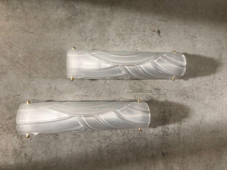 Stylish pair of hand casted translucent white Murano Glass sconces with brass details. Half cylinder shape with unique hand-carved details. Imported from Venice, Italy, circa 1970s Newly wired for U.S. use. This pair of sconces is on display at the