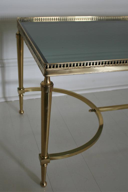 French vintage coffee or cocktail table in solid brass and smoked glass with finely cast galleries and original smoked glass. A very elegant and heavy piece with flawless cast details and a warm patina. Solid and sturdy.