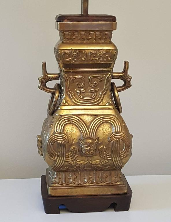 Incredible pair of massive Chinese style archaic bronze or brass urn vessels mounted as table lamps. Gorgeous antiqued patina completes the effect of these pieces. Each lamp weighs over 20 pounds and is made of solid bronze or brass except the wood