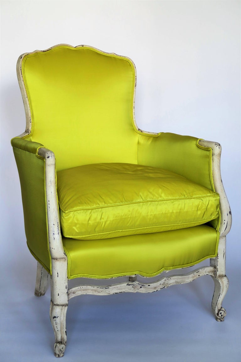 Beautiful pair of painted Bergeres chairs reupholstered in a modern Chartreuse Silk fabric with down cushions. Original frame painted in an oyster white with ladder back. Beautiful patina with chips and scratches to paint which gives this pair of