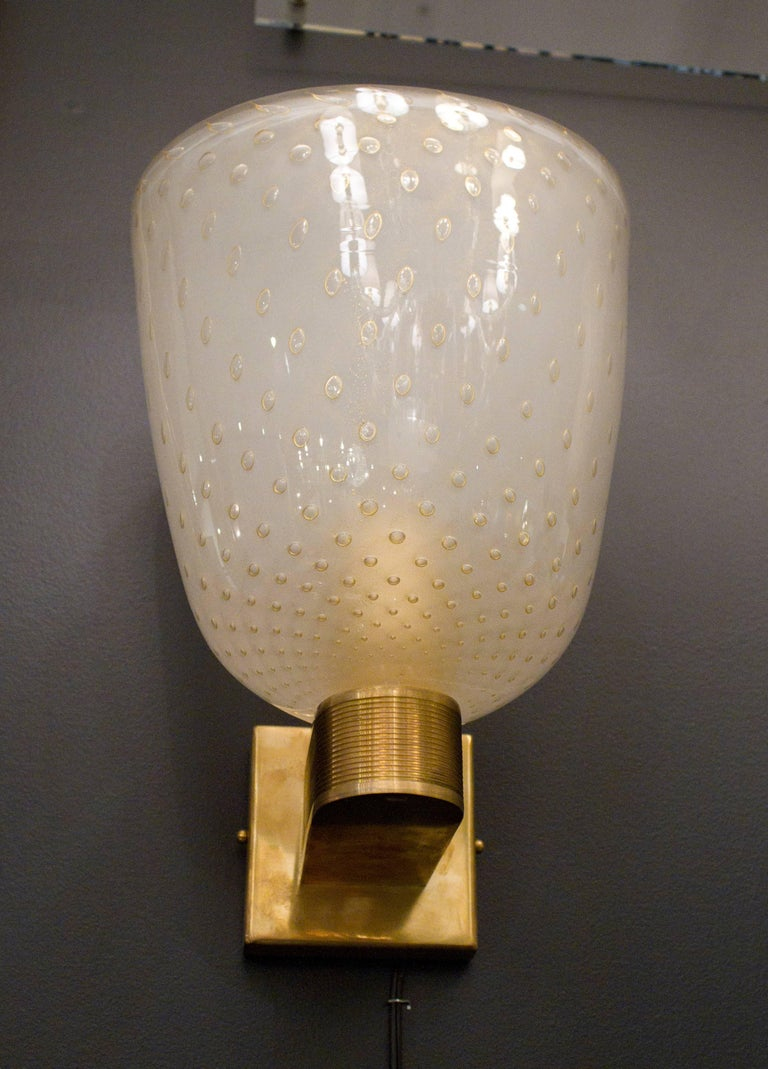 20th Century Pair of Italian Ivory and Gold Flecked Murano Glass and Brass Sconces For Sale