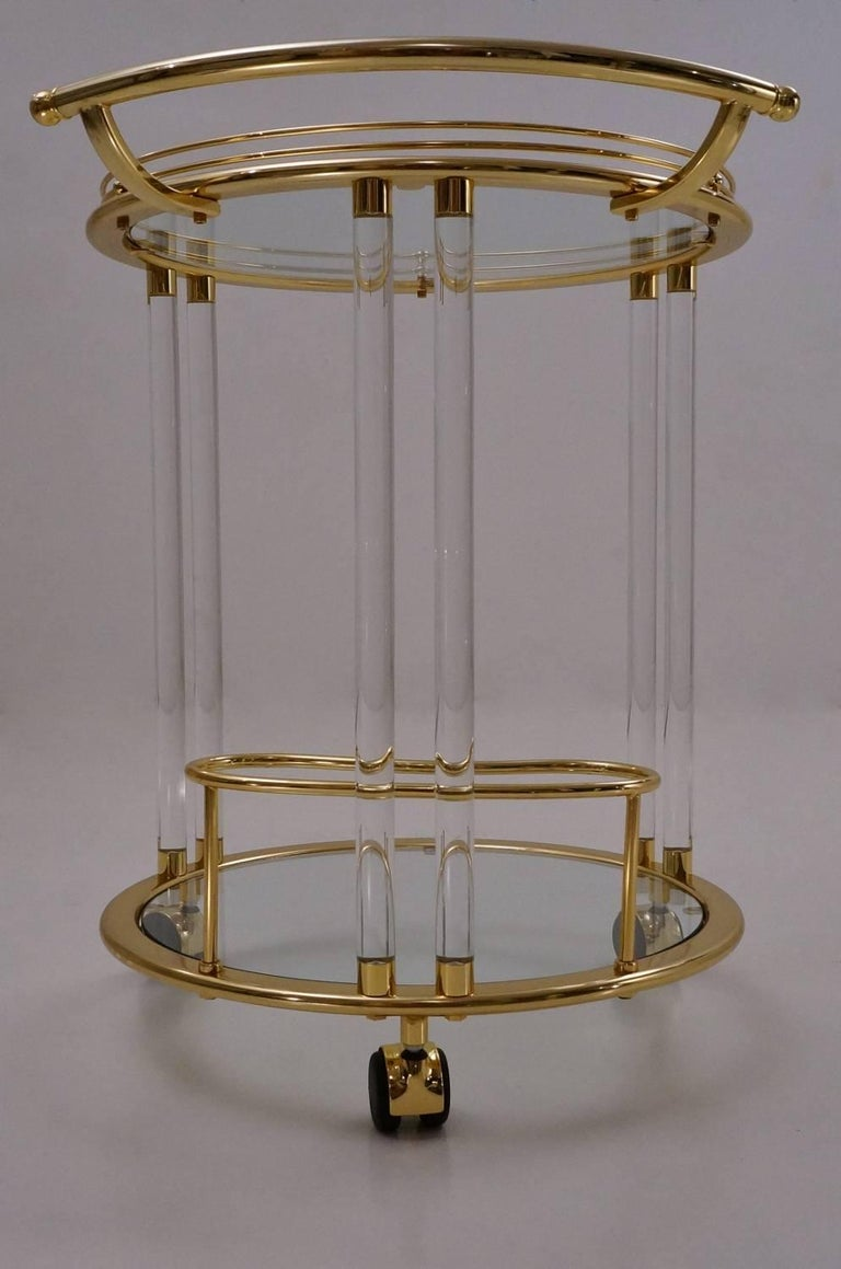 Orsenigo drinks or bar cart in gold-plated gilt with glass tops this vintage bar cart has a pared down neoclassical design. The Lucite columns are reminiscent of the earlier Art Deco period. Structurally there are two levels, a top and lower shelf,