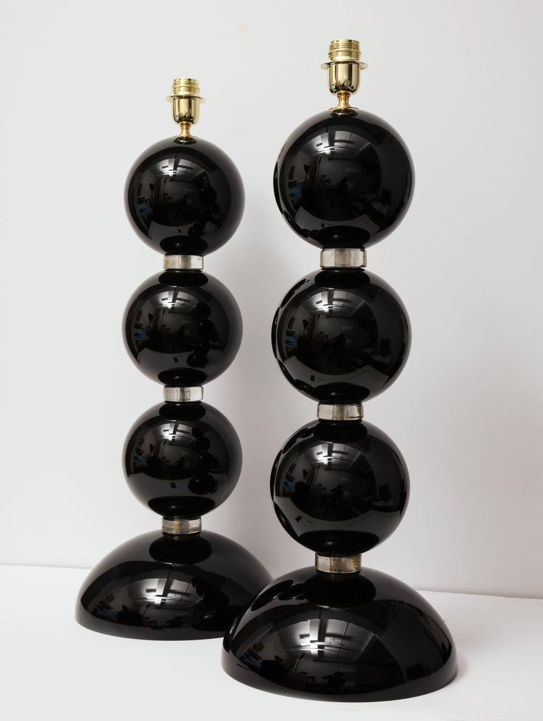 Classic yet edgy! This pair of Italian handblown Murano glass lamps combine timeless Classic design with a modern twist. Large solid black modern Murano glass spheres are separated by clear glass rings infused with 23-karat gold powder, giving them
