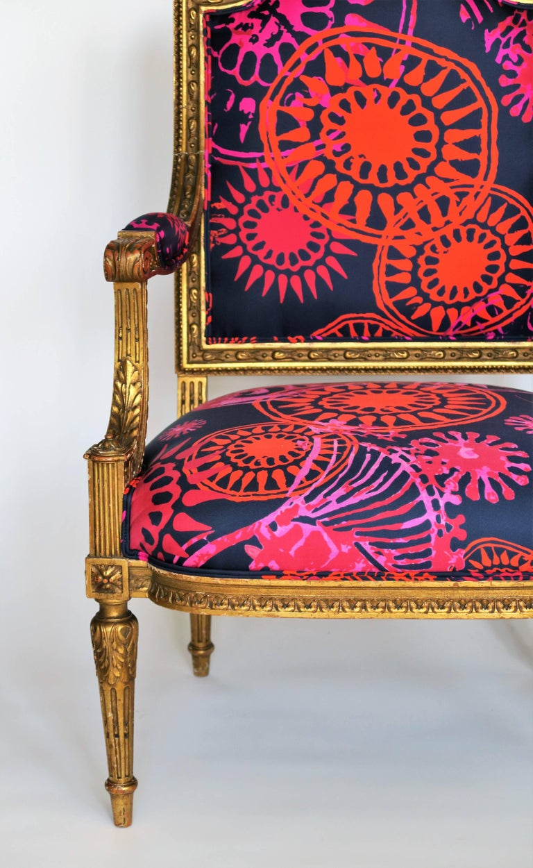 Breathtaking restoration of one gilded (gold) and hand-carved, late 19th century Louis XVI style armchair. The frame is original and shows beautiful gilded patina with chips and scratches commensurate with the chair's age and use. Stunning details.