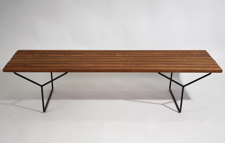 Early Harry Bertoia designed wood slat bench for Knoll International, circa 1960. Awesome form and design. Has wrought iron legs and the wood has wonderful color. In excellent original vintage condition. Tough to find early bench.