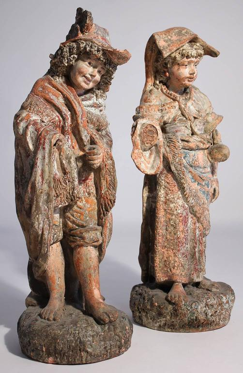 Wonderful pair of antique painted terracotta garden sculptures or figures with a perfectly aged and weathered patina. Each piece standing just over 2 feet tall.