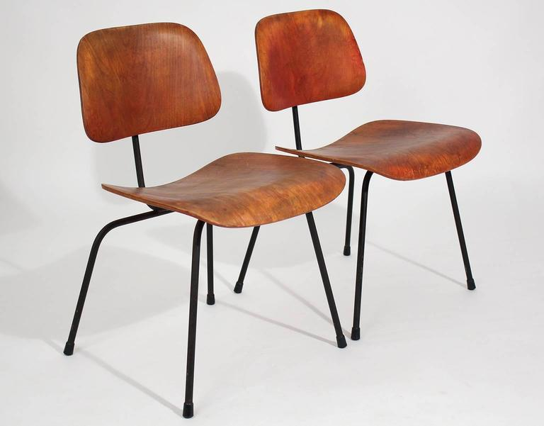 Great pair of early original Charles Eames for Herman Miller Aniline red DCM dining chairs with awesome patina. These are very early and would be great as accent chairs. The mounts are in great shape and are very strong. Patina is beautiful. Shows