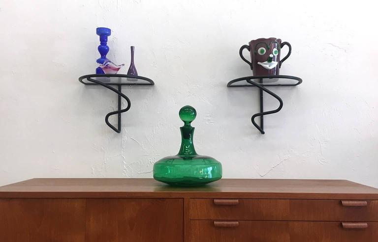 Modernist wrought iron pair of wall shelves with semi-circular glass inserts, circa 1950s. Iron section retains original finish in excellent vintage condition. New glass.